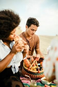 Amici che hanno un picnic sulla spiaggia estiva