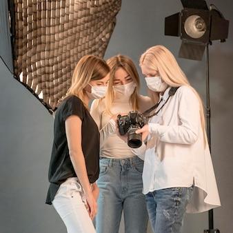 Amici che indossano le maschere mediche in uno studio