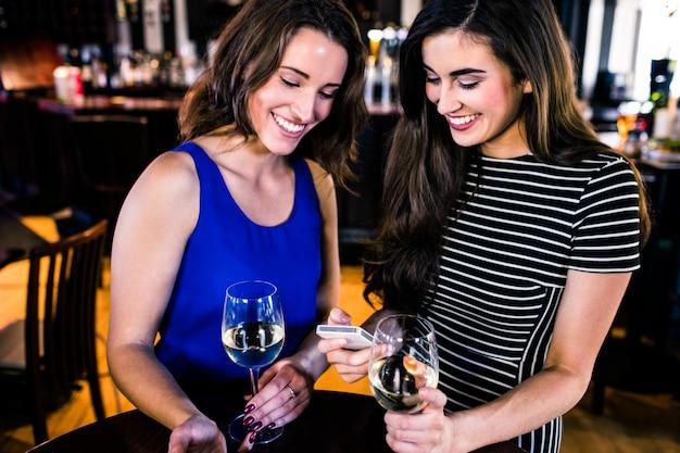 Amici che mandano un sms e che bevono un bicchiere di vino in un bar