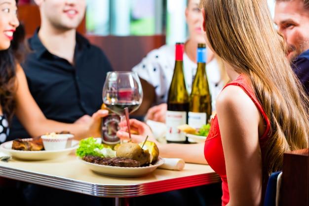 Amici che mangiano e bevono nella cena di fast food