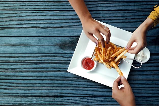 Amici che mangiano patatine fritte di patate francesi, servite su un setaccio in metallo con due tuffi