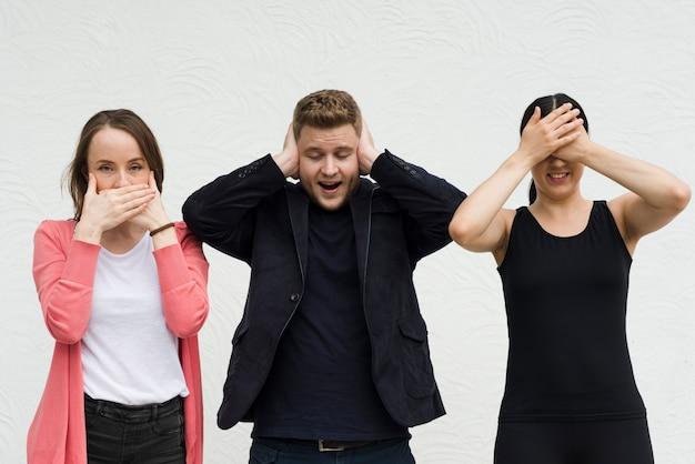Amici che mostrano i simboli di tre scimmie sagge