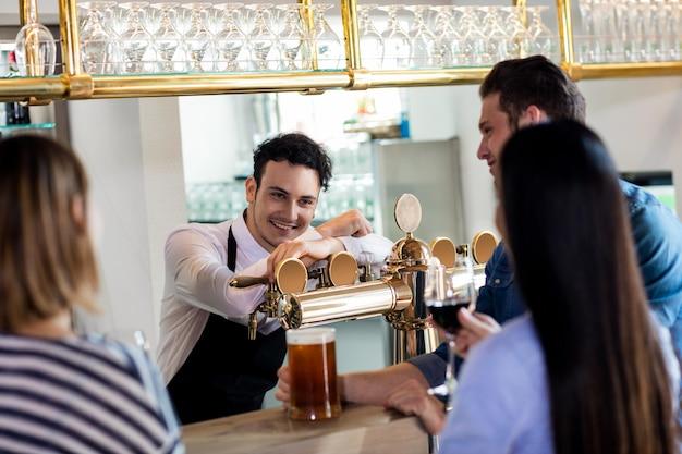 Amici che parlano con il barista mentre bevono