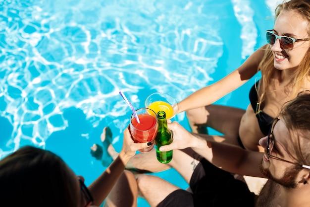 Amici che parlano, sorridono, bevono cocktail, riposano, si rilassano vicino alla piscina