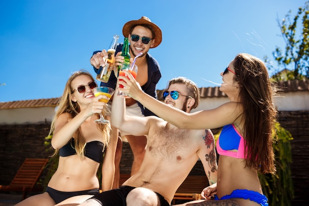 Amici che parlano, sorridono, bevono cocktail, riposano, si rilassano vicino alla piscina.