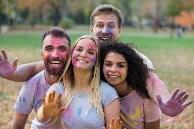 Amici che posano felicemente al festival di holi