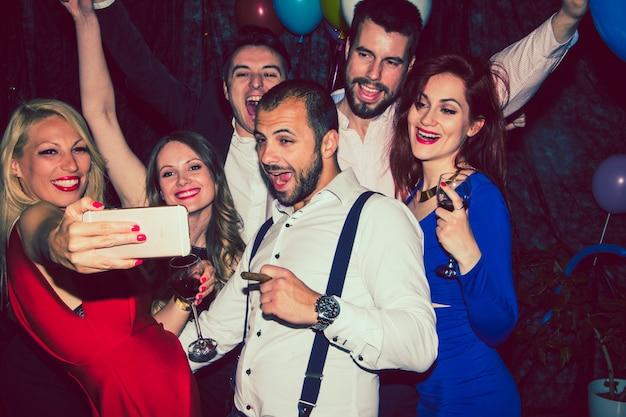 Amici che prendono selfie alla festa