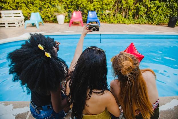Amici che prendono selfie in piscina