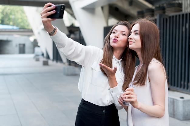 Amici che prendono un selfie in strada