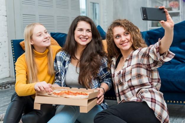 Amici che prendono un selfie mangiando pizza