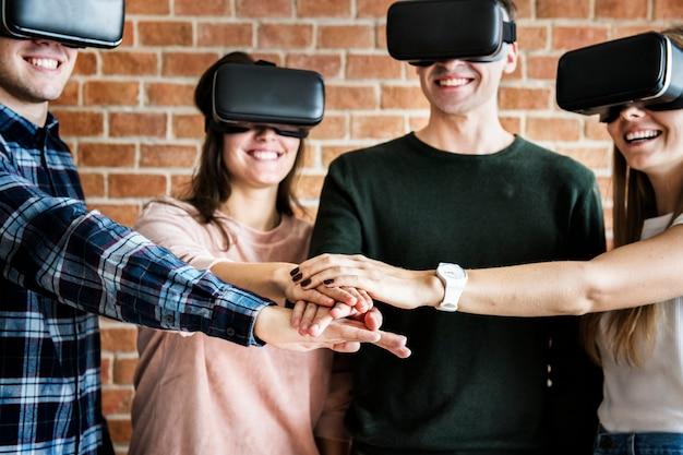 Amici che provano su cuffie e concetto di lavoro di squadra di realtà virtuale
