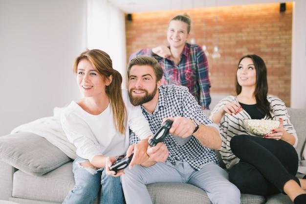 Amici che ridono in competizione con i videogiochi