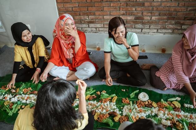 Amici che ridono mentre si mangia il pranzo a casa