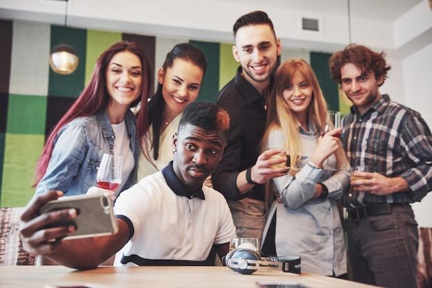 Amici che si divertono al ristorante. tre ragazzi e tre ragazze che fanno selfie e ridono. in primo piano ragazzo che tiene smart phone. tutti indossano abiti casual