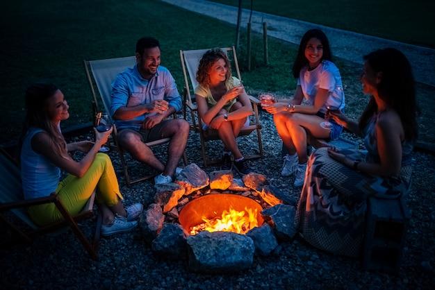 Amici che si divertono intorno al fuoco di notte.