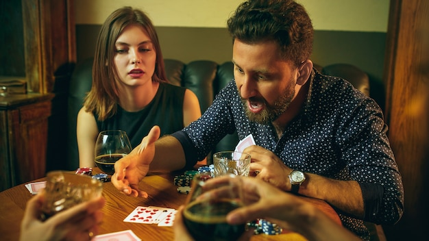 Amici che si siedono al tavolo di legno. amici che si divertono mentre giocano a gioco da tavolo.