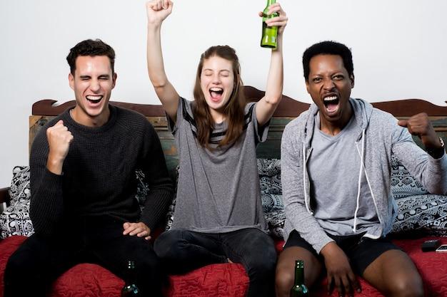 Amici che si siedono su sofa watching sport together