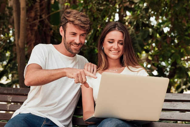 Amici che si siedono su una panchina con un computer portatile