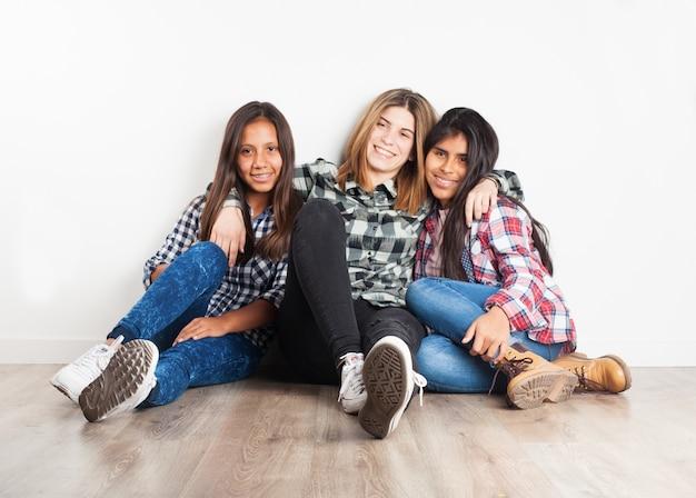 Amici che si siedono sul pavimento