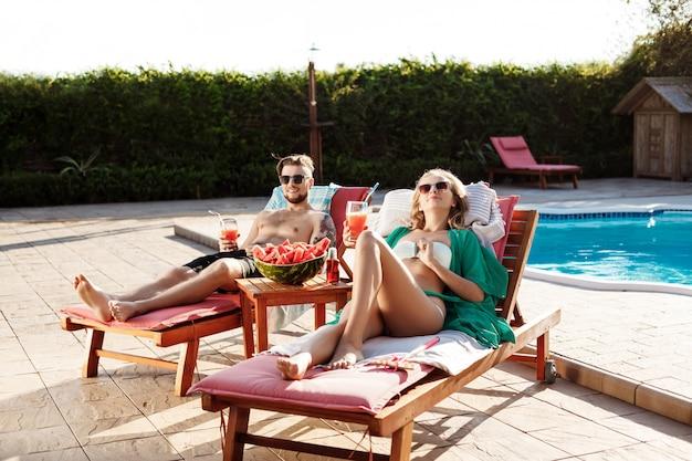 Amici che sorridono, bevendo cocktail, sdraiati su sedie a sdraio vicino alla piscina