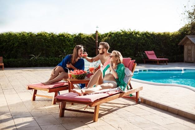 Amici che sorridono, mangiando anguria, relax, sdraiato vicino alla piscina