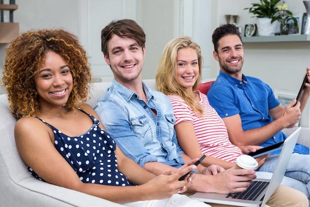 Amici che sorridono mentre usando le tecnologie sul sofà a casa