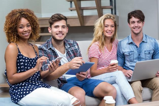 Amici che sorridono mentre usando le tecnologie sul sofà
