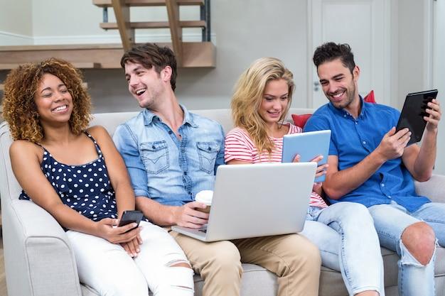 Amici che sorridono mentre utilizzano le tecnologie a casa