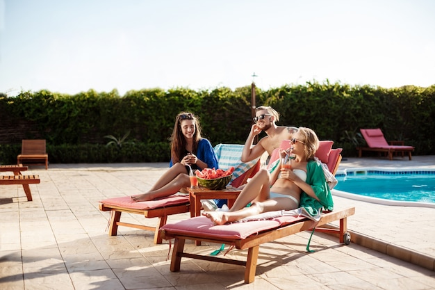 Amici che sorridono, riposano, bevono cocktail, sdraiati vicino alla piscina