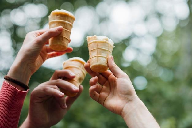 Amici che tengono il gelato in mani nel parco