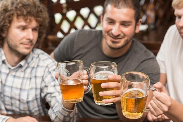 Amici che tintinnano i bicchieri al bar
