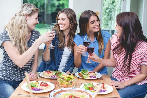 Amici che tostano bicchiere di vino rosso mentre consumano il pasto