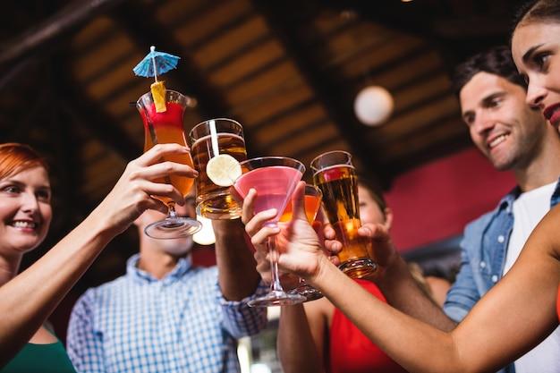 Amici che tostano bicchieri da bere in discoteca