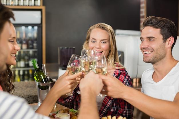 Amici che tostano con bicchieri di vino bianco