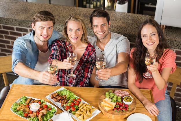 Amici che tostano con il vino bianco