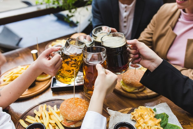 Amici che tostano con la birra nel ristorante