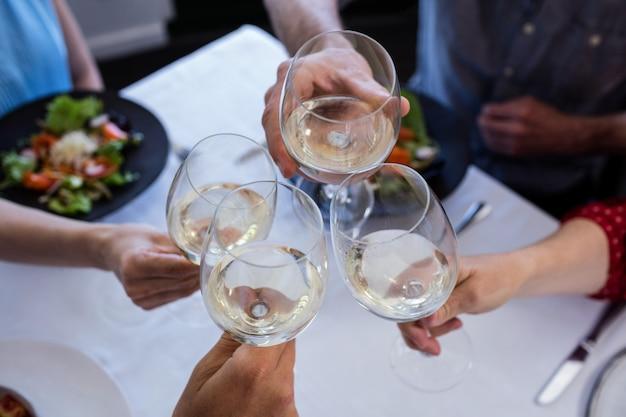 Amici che tostano il bicchiere di vino mentre pranzano