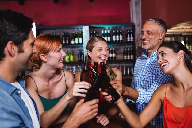 Amici che tostano la bottiglia di birra in discoteca