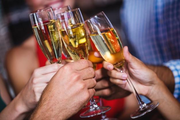 Amici che tostano un bicchiere di champagne in discoteca