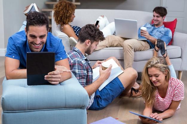 Amici che utilizzano le moderne tecnologie nel soggiorno