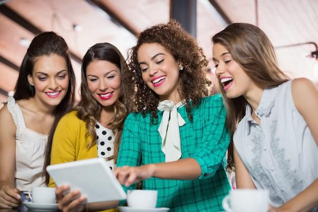 Amici che utilizzano tavoletta digitale nella caffetteria