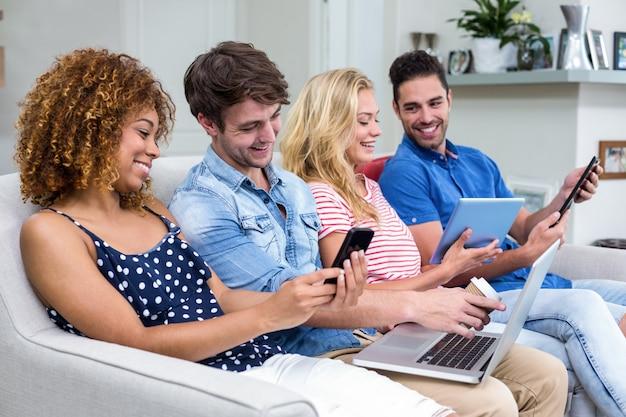 Amici che utilizzano tecnologie sul divano