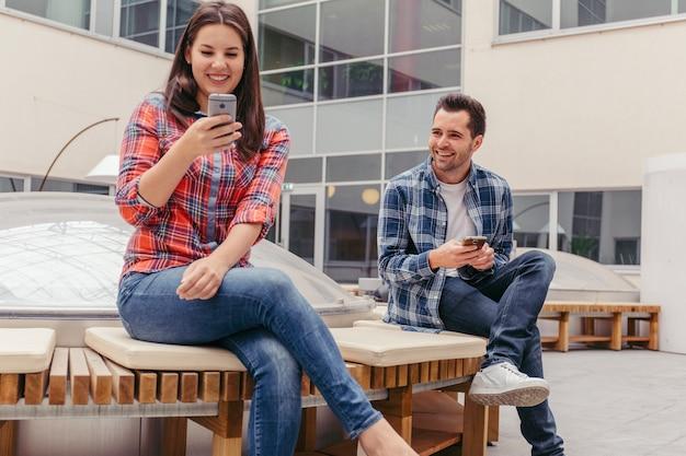 Amici che utilizzano telefoni e seduti sul banco
