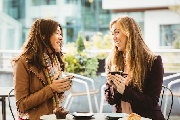 Amici chiacchierando davanti a un caffè nella caffetteria
