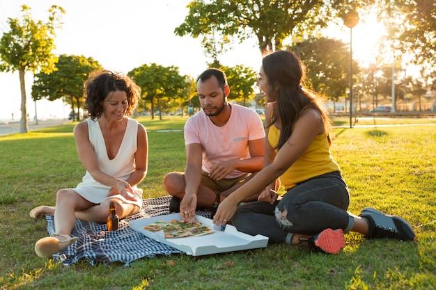 Amici chiusi felici che mangiano pizza in parco