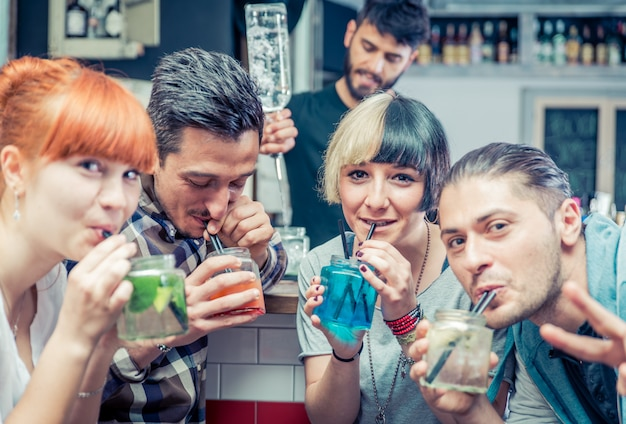 Amici con cocktail in un bar