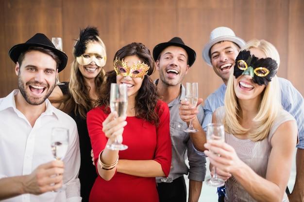 Amici con maschere sul possesso di bicchieri di champagne che ridono della fotocamera