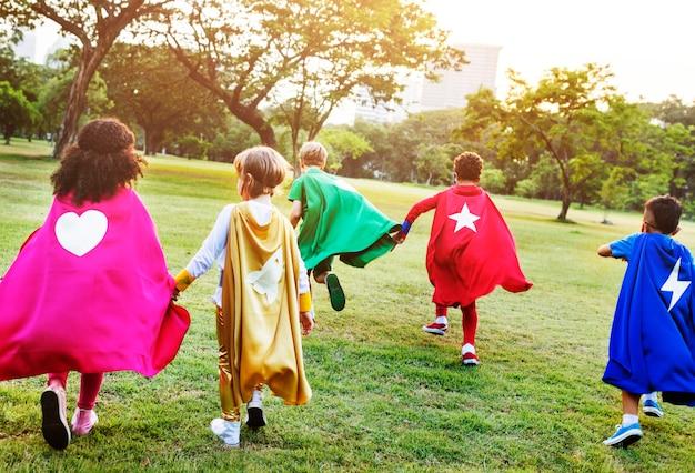Amici dei bambini dei supereroi che giocano concetto di divertimento di unità