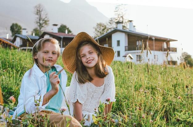 Amici dei fratelli e delle sorelle dei bambini che si siedono nell'erba contro lo sfondo di belle case in montagna, viaggio della famiglia, scena rurale