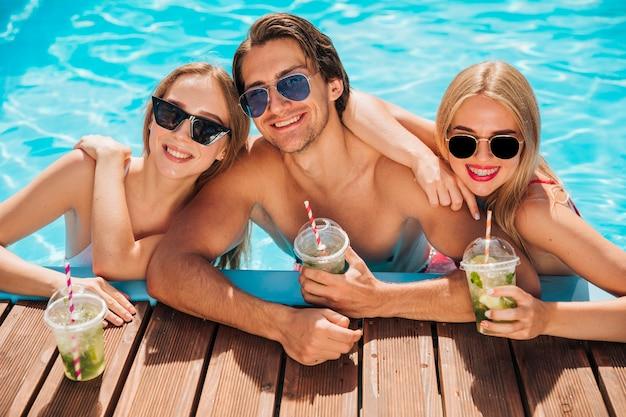 Amici del colpo medio che esaminano macchina fotografica nella piscina